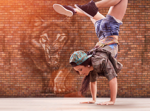 Dancer doing back flip, tiger street art in backgroundの写真素材 [FYI03805979]