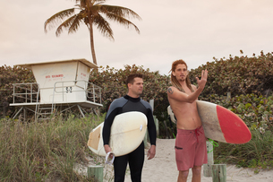 Male lifeguard having discussion with surfer on beachの写真素材 [FYI03806032]