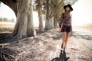 Young woman in boho style and felt hat strolling on roadsideの写真素材 [FYI03806034]