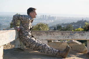 Soldier wearing combat clothing doing reverse push up, Runyon Canyon, Los Angeles, California, USAの写真素材 [FYI03806055]