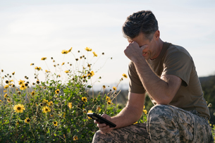 Soldier wearing combat clothing looking at smartphone, Runyon Canyon, Los Angeles, California, USAの写真素材 [FYI03806056]