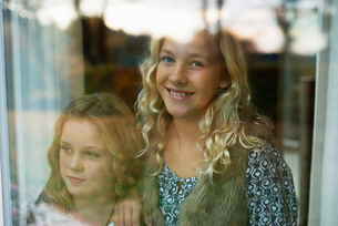 Portrait of two sisters looking through windowの写真素材 [FYI03806093]