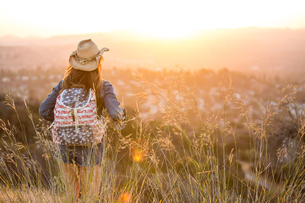 Woman hiking, wearing stars and stripes backpack, rear viewの写真素材 [FYI03806185]