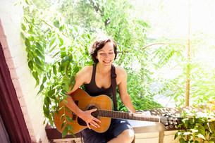 Woman playing guitar on balconyの写真素材 [FYI03806190]