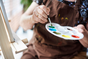Woman holding palette with brush and paintsの写真素材 [FYI03806256]