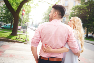 Rear view of couple walking in street arms around each otherの写真素材 [FYI03806276]