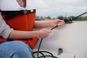 Woman on sailing boat, steering boat, close-upの写真素材 [FYI03806282]