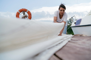 Young woman folding boat's sailの写真素材 [FYI03806295]