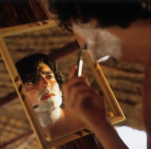Mirror image of man shavingの写真素材 [FYI03806321]