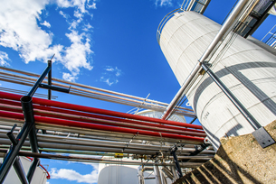 Low angle view of industrial piping and storage tanks at biofuel plantの写真素材 [FYI03806403]