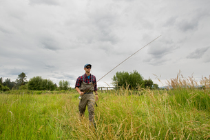 Fisherman with fishing rod on grass field, Clark Fork, Montana and Idaho, USの写真素材 [FYI03806446]