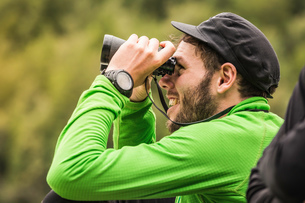 Young male backpacker looking through binoculars in Queulat National Park, Chileの写真素材 [FYI03806472]