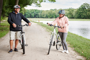 Mature couple walking along rural pathway with bicycles, smilingの写真素材 [FYI03806539]