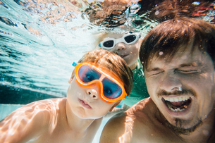 Portrait of father and sons, under water, underwater viewの写真素材 [FYI03806556]