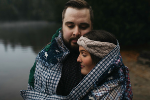 Couple wrapped in blanket eyes closed huggingの写真素材 [FYI03806587]