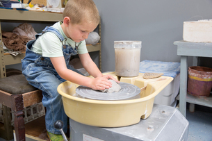 Boy shaping clay on potter's wheelの写真素材 [FYI03806700]