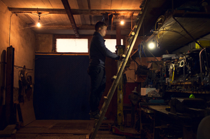 Mechanic on ladder looking at shelves in workshopの写真素材 [FYI03806767]