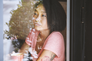 Woman gazing in cafe window seat, Shanghai French Concession, Shanghai, Chinaの写真素材 [FYI03806772]