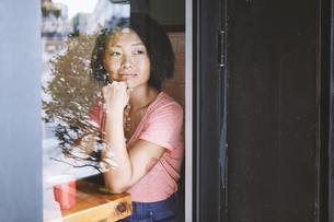 Woman gazing through cafe window, Shanghai French Concession, Shanghai, Chinaの写真素材 [FYI03806777]