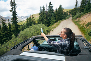 Young woman on road trip taking smartphone selfie travelling in convertible, Breckenridge, Colorado,の写真素材 [FYI03806816]
