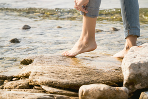 Cropped view of woman barefoot on rocksの写真素材 [FYI03806828]