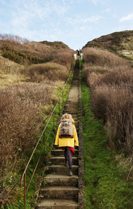 Girl with retro backpack moving up stairway near former NATO fuel station on Normandy coastの写真素材 [FYI03806891]