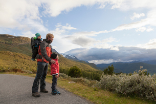 Man with sons looking out at mountain landscape, Jotunheimen National Park, Lom, Oppland, Norwayの写真素材 [FYI03806920]