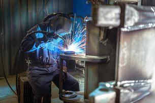 Welder welding part of digger bucket in engineering factoryの写真素材 [FYI03806937]