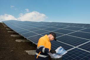 Engineer connecting solar panels on new solar farm, situated on former waste dumpの写真素材 [FYI03806941]