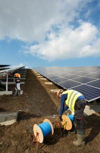 Engineers connecting solar panels on new solar farm, situated on former waste dumpの写真素材 [FYI03806947]
