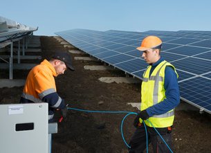 Engineers connecting solar panels on new solar farm, situated on former waste dumpの写真素材 [FYI03806948]