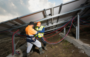 Engineers connecting solar panels on new solar farm, situated on former waste dumpの写真素材 [FYI03806951]