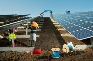 Engineers connecting solar panels on new solar farm, situated on former waste dumpの写真素材 [FYI03806952]