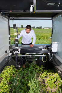 Man checking on robot monitoring crops and flowers on agricultural site in pixelfarming researchの写真素材 [FYI03807051]