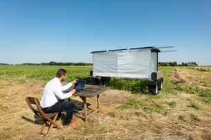 Man checking on robot monitoring crops and flowers on agricultural site in pixelfarming researchの写真素材 [FYI03807059]
