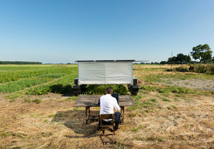 Man checking on robot monitoring crops and flowers on agricultural site in pixelfarming researchの写真素材 [FYI03807060]