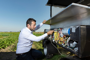 Man checking on robot monitoring crops and flowers on agricultural site in pixelfarming researchの写真素材 [FYI03807065]