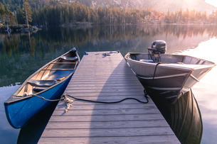 Canoe and motor boat moored at wooden pier on Echo Lake, High Sierras, California, USAの写真素材 [FYI03807074]