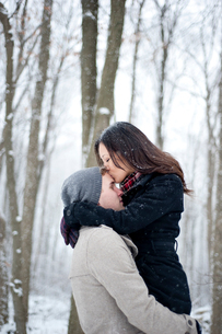 Romantic young woman kissing boyfriend's forehead in snow covered forest, Ontario, Canadaの写真素材 [FYI03807221]