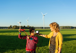 Teenage boy and girl experimenting with sustainable energy by wind turbines, Netherlandsの写真素材 [FYI03807237]