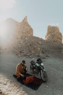 Motorcyclist with toolbox beside bike, Trona Pinnacles, California, USの写真素材 [FYI03807290]