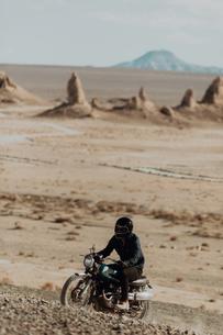 Motorcyclist riding in desert, Trona Pinnacles, California, USの写真素材 [FYI03807291]