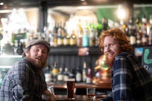 Two male customers looking over their shoulders from bar in traditional Irish public houseの写真素材 [FYI03807296]