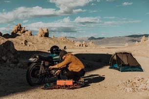 Motorcyclist fixing bike beside tent, Trona Pinnacles, California, USの写真素材 [FYI03807298]
