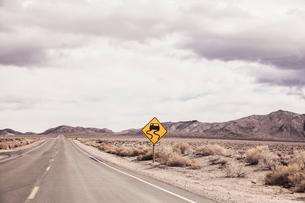 Arid landscape with yellow warning sign on roadside, Keeler, California, USAの写真素材 [FYI03807354]
