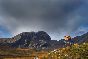Male mountain biker biking down mountain landscape,  Achnasheen, Scottish Highlands, Scotlandの写真素材 [FYI03807399]