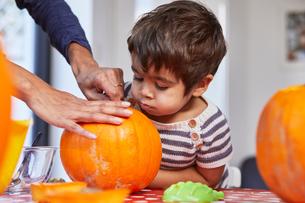 Boy looking at mother gut pumpkin in kitchenの写真素材 [FYI03807407]