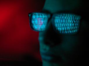 Cyber Crime, reflection in spectacles of virus hacking a computer, close up of faceの写真素材 [FYI03807423]