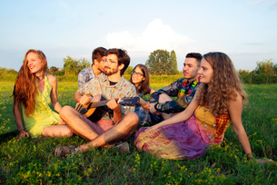 Group of young adults sitting in field listening to acoustic guitarの写真素材 [FYI03807595]