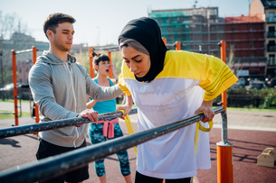 Calisthenics class at outdoor gym, male trainer encouraging young woman on parallel barsの写真素材 [FYI03807612]